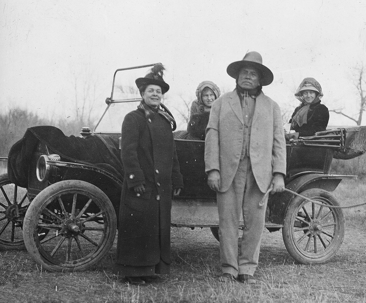 Miss Crawford, missionary to Kiowas, with Curley (Custer Scout); Anna and Genevieve Petzoldt in car, Montana, ca. 1903–1925. MS 95 William A. Petzoldt Lantern Slide Collecction. LS.95.143