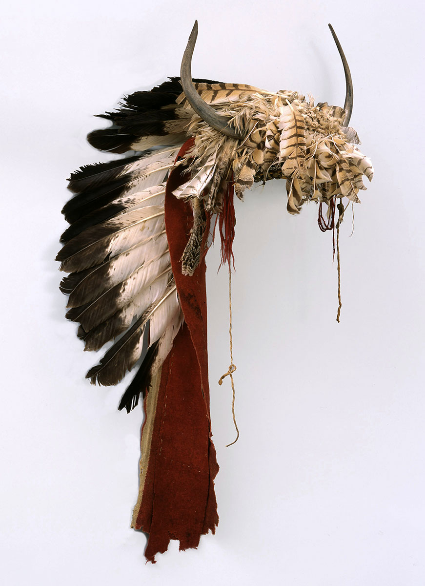 Buffalo horn bonnet, ca. 1860. Northern Plains, Crow. Feathers, wool, glass beads, bells, deer hide, brass, buffalo, eagle, horns. Catherine Bradford McClellan Collection, Gift of The Coe Foundation. NA.203.18