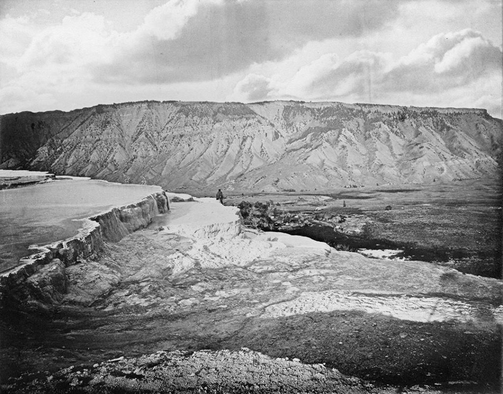 Yellowstone as revealed through the Albertype prints of William Henry Jackson. In this example, we see Mammoth Hot Springs, Mt. Everts in the background, the painter Thomas Moran posed on a ledge, and the negative altered to show puffy clouds. It is all there, the detail, the composition, the art, and the beauty of Jackson's Yellowstone. WHJ-A.064