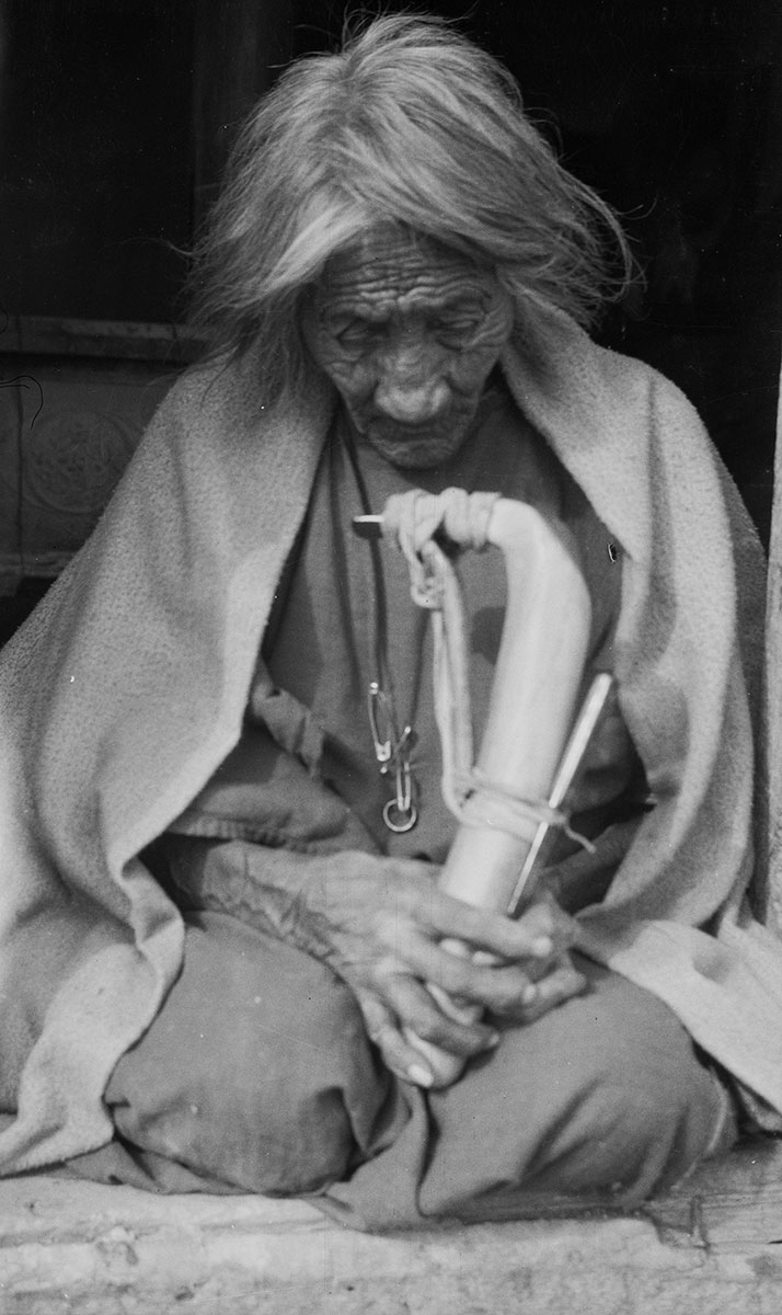 Cheyenne woman kneeling with a hide scraper in her hands, ca. 1922–1935. MS 165 Thomas Marquis Native American Nitrate Negative Collection. PN.165.1.77
