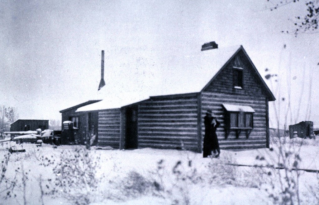 Absarokee Hut in winter, ca. 1905. Addie Sharp stands on the front walk, holding her dog Frans Hals. P. 22.523