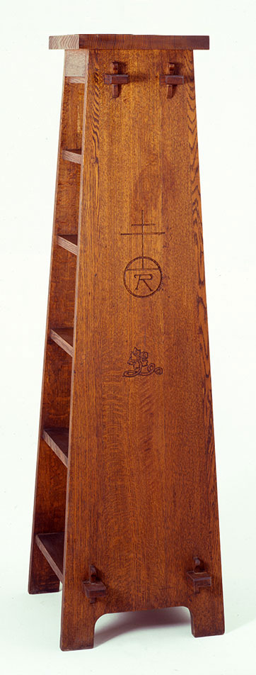"""Sharp's oak Roycroft magazine pedestal, ca. 1905. Visible joints on the side show how the piece was constructed. Such """"revealed design"""" elements are a common characteristic of Arts and Crafts furniture. The pedestal also bears the Roycroft mark, an orb and cross. Height 64 inches. 19.00.79"""