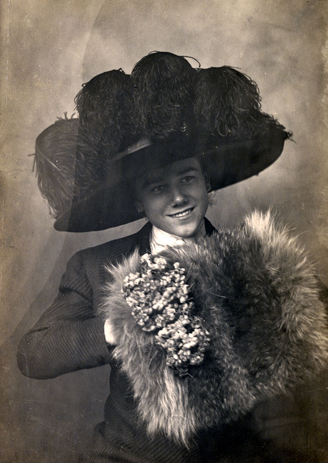"""Teasing his sisters, Cody Bell tries on his mother's hat and muff for the camera, about 1910. Cody told a journalist, """"It gets annoying to be always mistaken for a girl...but I keep them guessing all the time."""" MS 294 Bell Family Collection. P.294.24"""