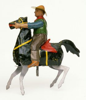 """A toy cowboy on a windowsill, part and parcel of a youngster's dreams of the West. """"The Bucking Broncho,"""" ca. 1932. The likeness of Buffalo Bill in a tin toy. Gift of Christopher and Rene Turner. 1.69.6014.1"""
