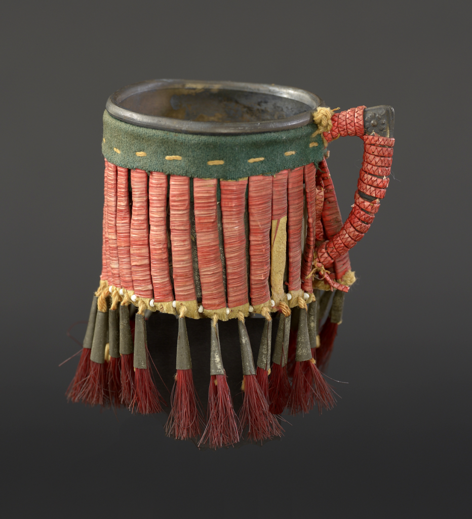 Cup, Lakota (Sioux), Northern Plains, ca.1900. Metal, rawhide, tin cones, glass beads, porcupine quills, tanned hide, wool cloth, cotton thread, dyed horse hair; NA.506.146. Courtesy of the Plains Indian Museum.