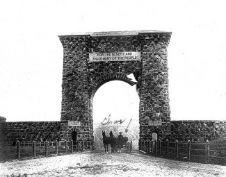 Frank J. Haynes photograph of Roosevelt Arch. Charles Ackelmire identified as man in wagon. MS 21 Yellowstone National Park Collection, McCracken Research Library, Buffalo Bill Center of the West. 21.217.12