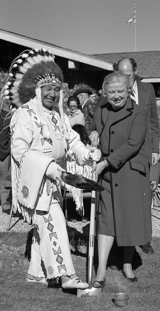 """Fig. 11: Plains Indian Museum groundbreaking, October 12, 1977, with Blackfeet member of the first Plains Indian Museum Advisory Board Peter Red Horn, Margaret """"Peg"""" Coe, and Al Simpson standing behind. MS 089 Jack Richard Photograph Collection, McCracken Research Library. PN.89.79.13527.12 (detail)"""