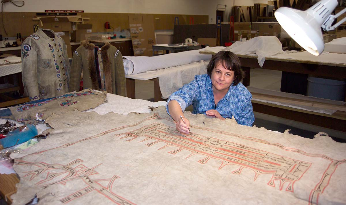Beverly Perkins treats a painted hide in the Center's conservation laboratory.