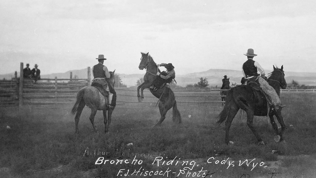 Arthur Holman bronc riding at Stampede Rodeo, Clarence William at left, Blocker Dodge at right. MS 005 Cody Local History Collection, McCracken Research Library. P.69.1703