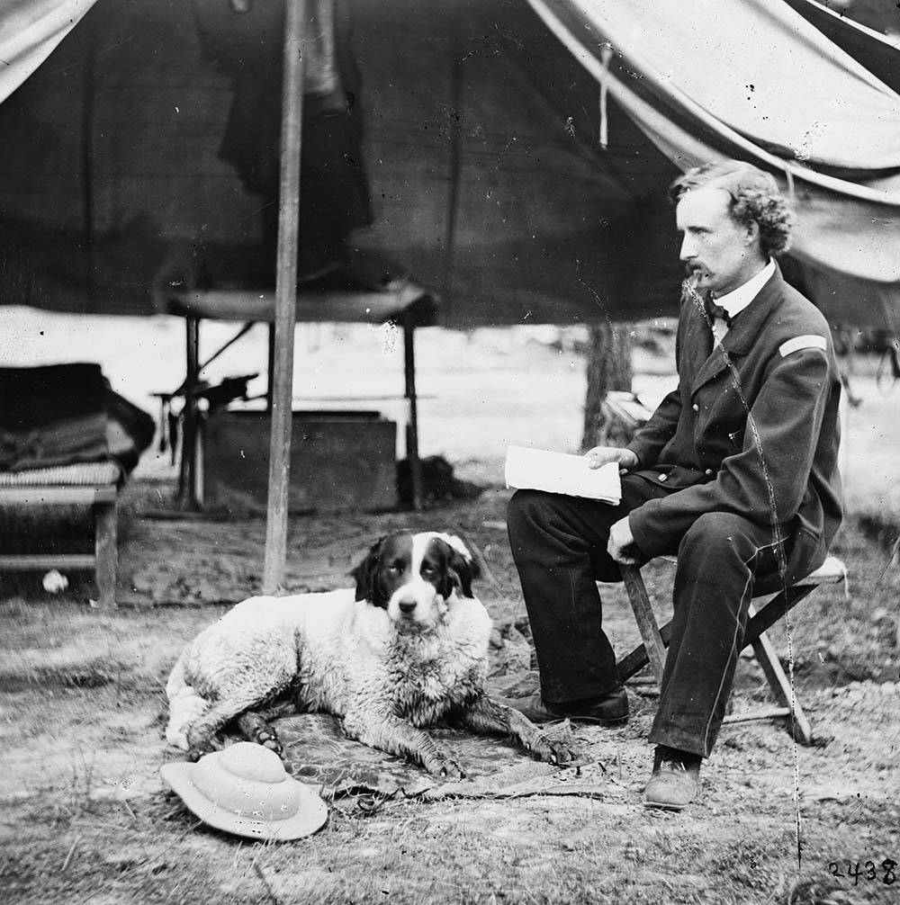George Armstrong Custer in camp during the summer of 1862 with a gun dog lounging on a rug. Prints & Photographs, Library of Congress, LC-B811-2344.