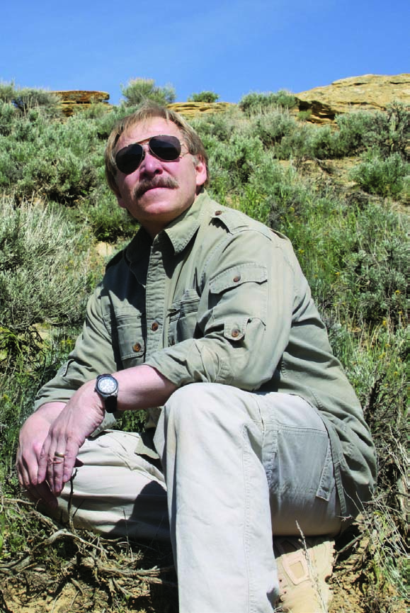 The author examines the site where a golden eagle parent captured a small prairie rattlesnake. Photo by Richard Jones.