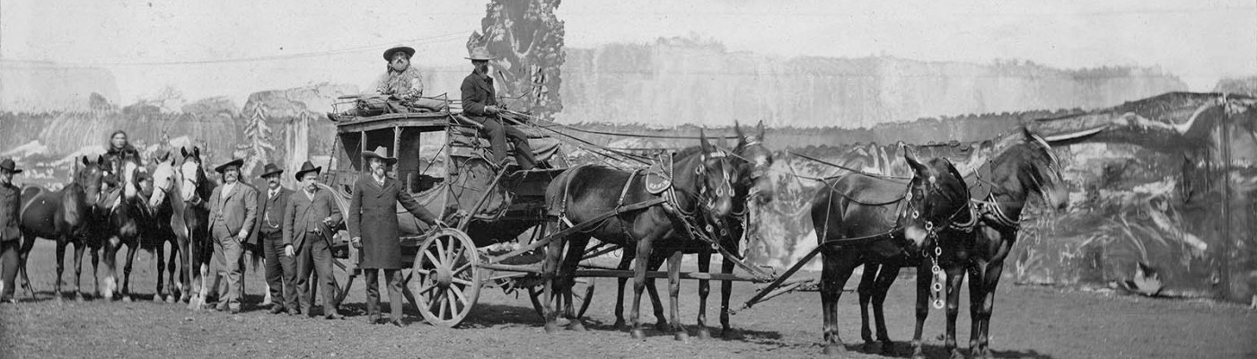 Buffalo Bill, with hand on wheel, and Major Burke, holding the first horse behind the coach, pictured with Wild West show personnel and the Deadwood Coach, ca. 1890. MS 6 William F. Cody Collection, McCracken Research Library. P.69.89
