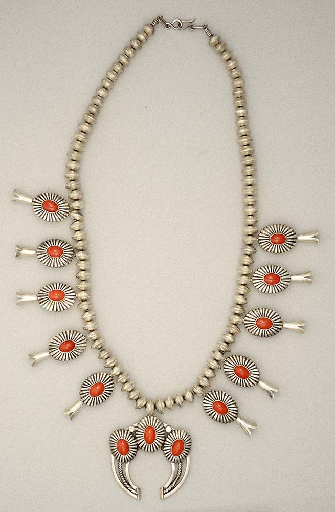 This necklace exemplifies Walsh's attraction to contemporary American Indian silver artists. This silver and coral squash blossom necklace was created by Navajo silversmith Thomas Jim late 20th century. Gift of Margo Grant Walsh, in Appreciation of Ann Simpson. 1.69.6360