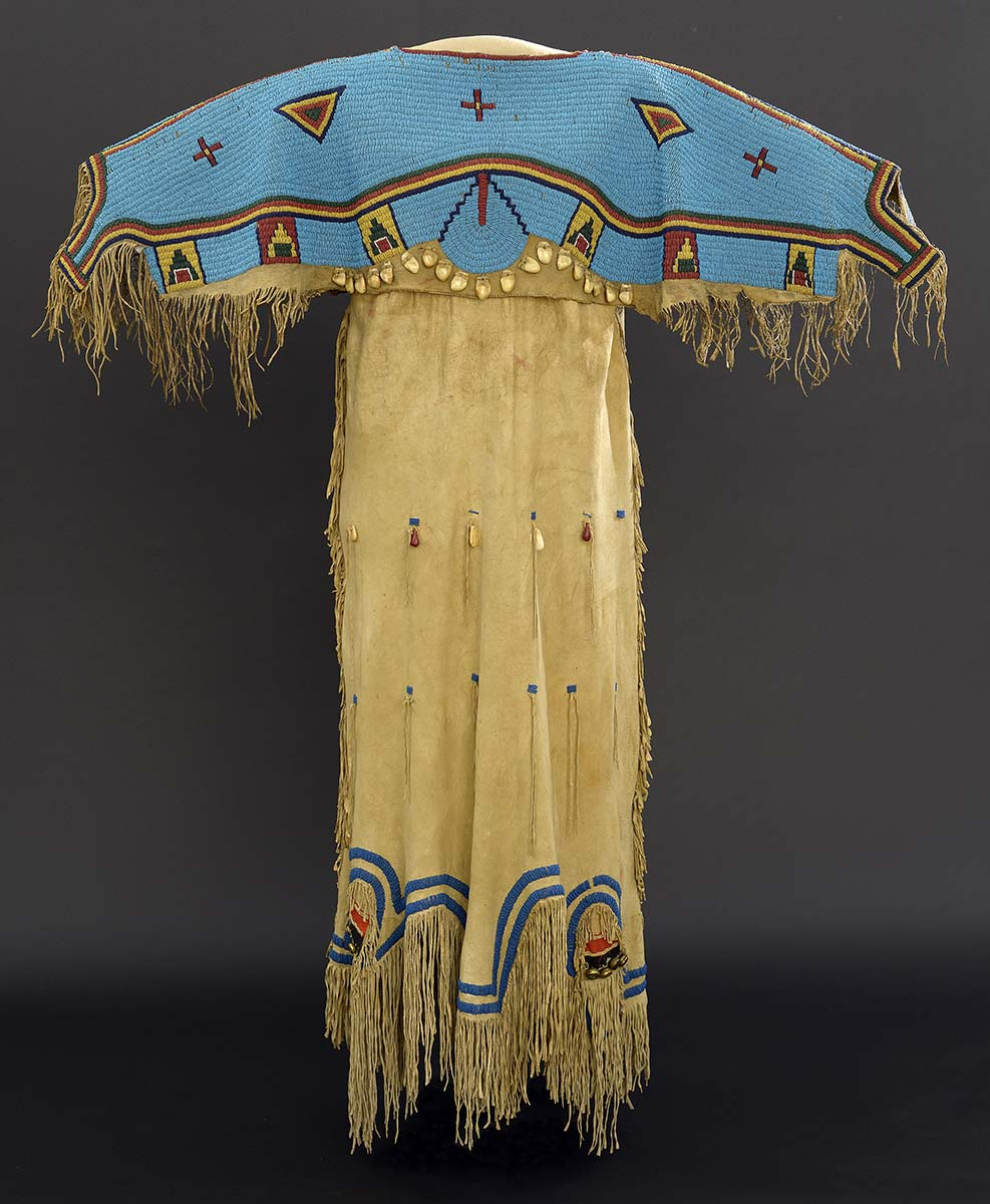 Fig. 8: One of the hundreds of treasures in the Paul Dyck Collection. Nineteenth-century dress of tradecloth, tanned hide, brass bells, beads, and elk teeth. The Paul Dyck Plains Indian Buffalo Culture Collection, acquired through the generosity of the Dyck family and additional gifts of the Nielson Family and the Estate of Margaret S. Coe. NA.202.1254