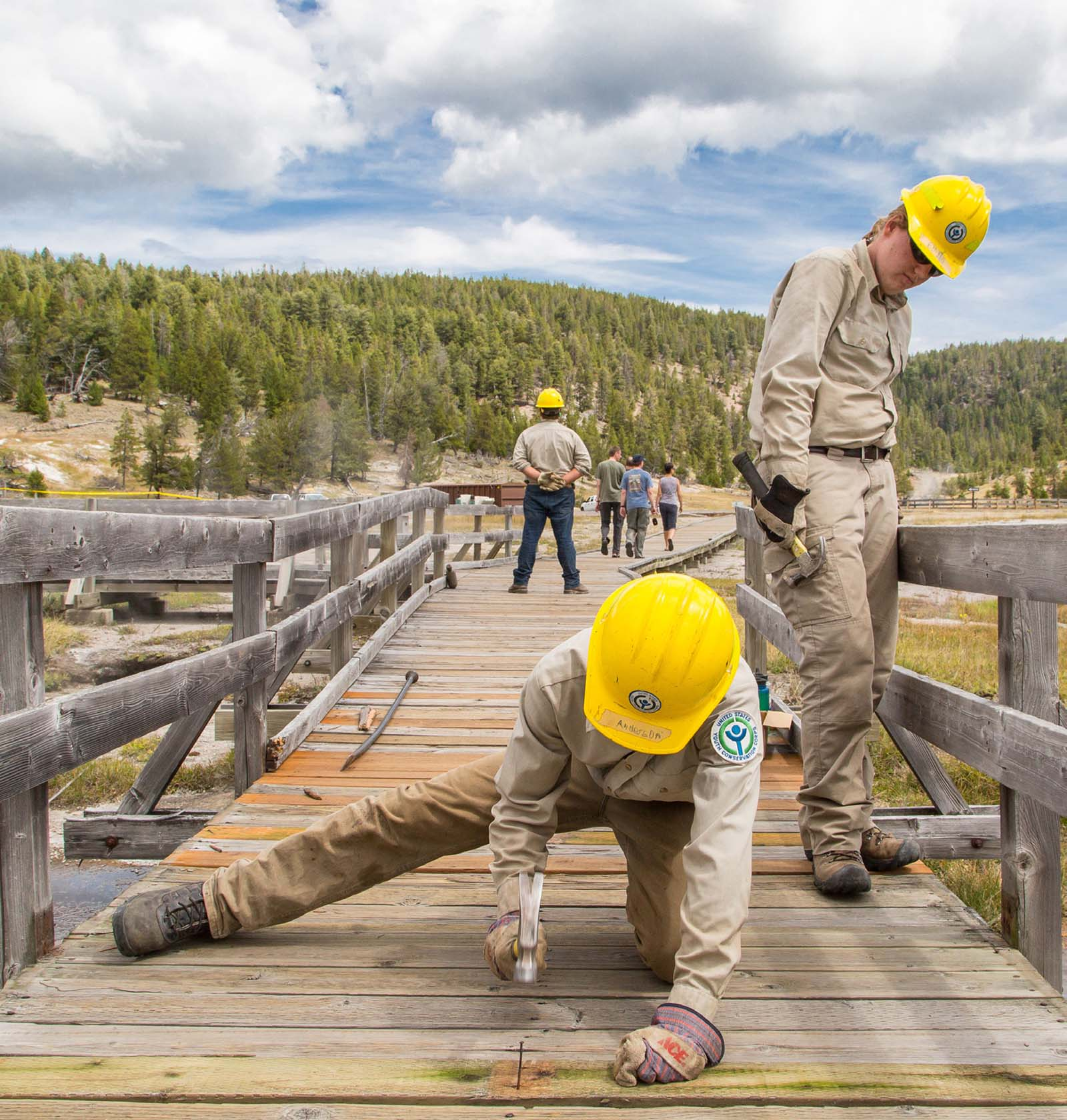 Youth Conservation Corps volunteers replace bridge planks. NPS photo/Neal Herbert.