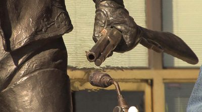 "Heating rifle barrel on ""Plainsman"" to reapply shiny coloration. Bob Scriver (1914-1999). ""Buffalo Bill—Plainsman,"" 1976. Cast by Modern Art Foundry, N.Y. Bronze, 86.5 x 62 x 50.25 inches. 12.77"