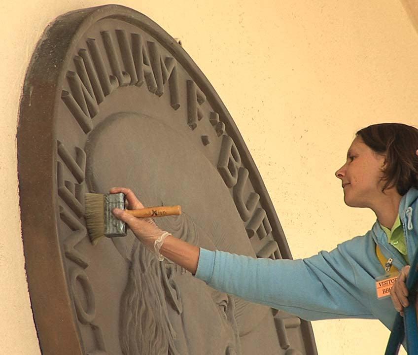 Marianne Marti cleaning bronze medallion.