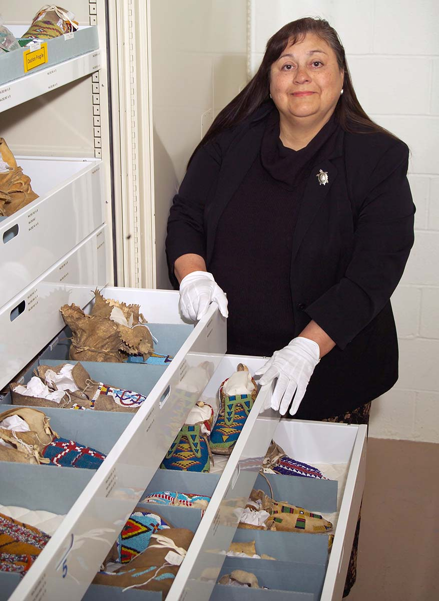 Plains Indian Museum Curator [now Curator Emerita] Emma Hansen reviews the museum's moccasins, carefully stored to prevent damage.