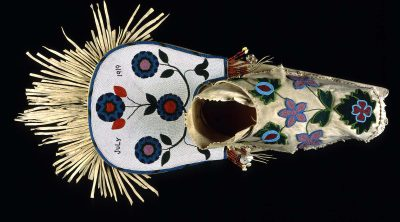 Cradleboard, Salish, Plateau 1919. Wood, tanned hide, muslin, glass beads, cowrie shells, abalone shells, mother of pearl, brass Simplot Collection, Gift of J.R. Simplot; NA.111.57