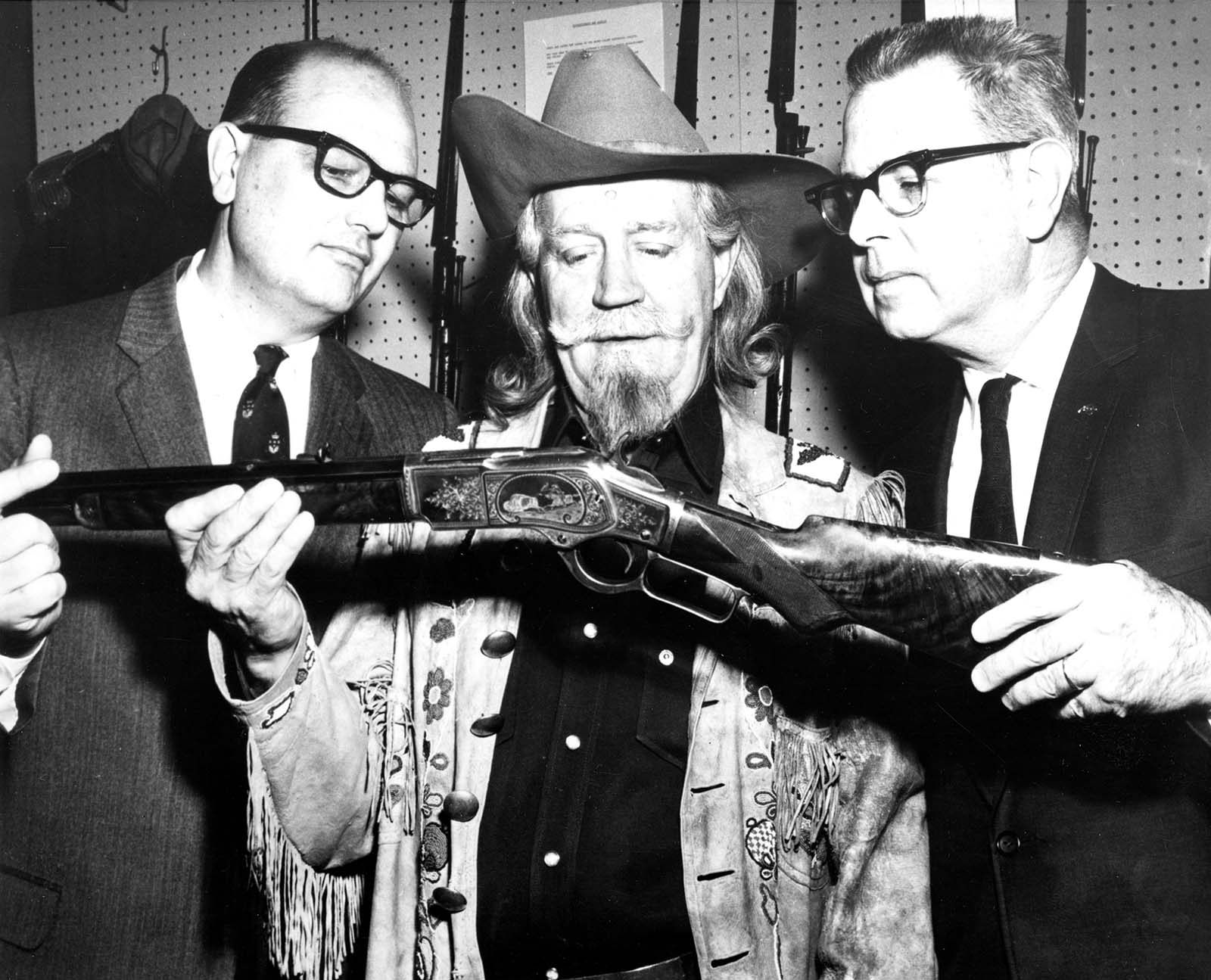 """Buffalo Bill's grandson Fred W. Garlow (center) pays a visit to the Winchester Arms Museum in New Haven, Connecticut, while traveling on behalf of the Center in 1968 to appear on the """"Today Show"""" in New York City. He shares his grandfather's Winchester 1873 rifle with Jack R. Peat, vice president of marketing for the Olin Corporation's Winchester-Western Division (left) and Tom Hall, museum curator. P.20.2618"""