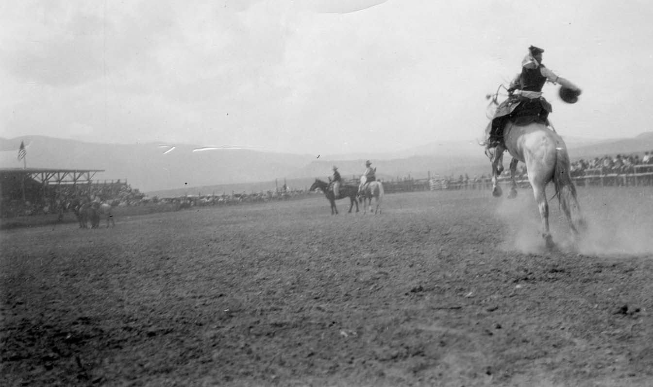Champion rider and local boy Nick Knight rides at the Cody Stampede, ca. 1935. Grandstands on left. Photo courtesy the Park County Archives. P86-016-12