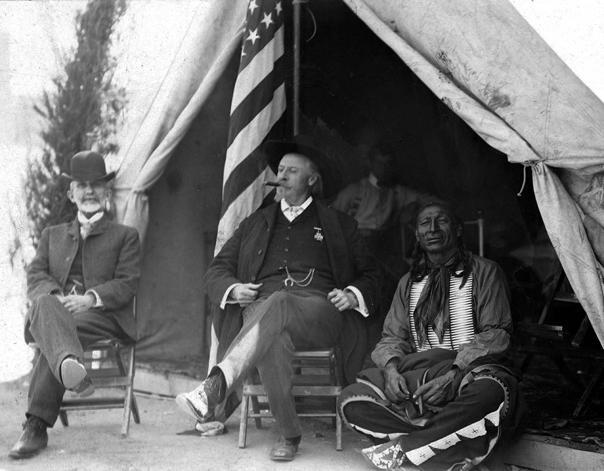 Nate Salsbury's work with Buffalo Bill's Wild West afforded him the experience to strategize a new exhibition, Black America. Here he's pictured with William F. Cody and Chief Iron Tail, ca. 1900, in front of Wild West show tent. MS 6 William F. Cody Collection, McCracken Research Library. P.69.1020