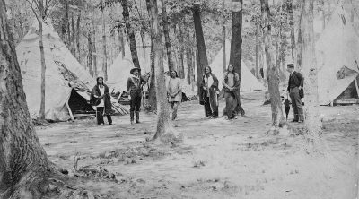 Wild West's Buck Taylor with the show's Indian encampment on Erostina Staten Island, ca. 1888. MS 006 William F. Cody Collection, McCracken Research Library. P.6.201