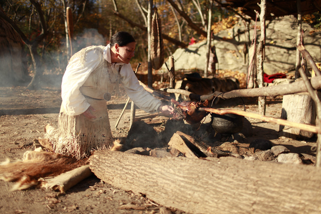 A reenactment presented as a living history exhibit of how turkeys were roasted on a stick over a fire.