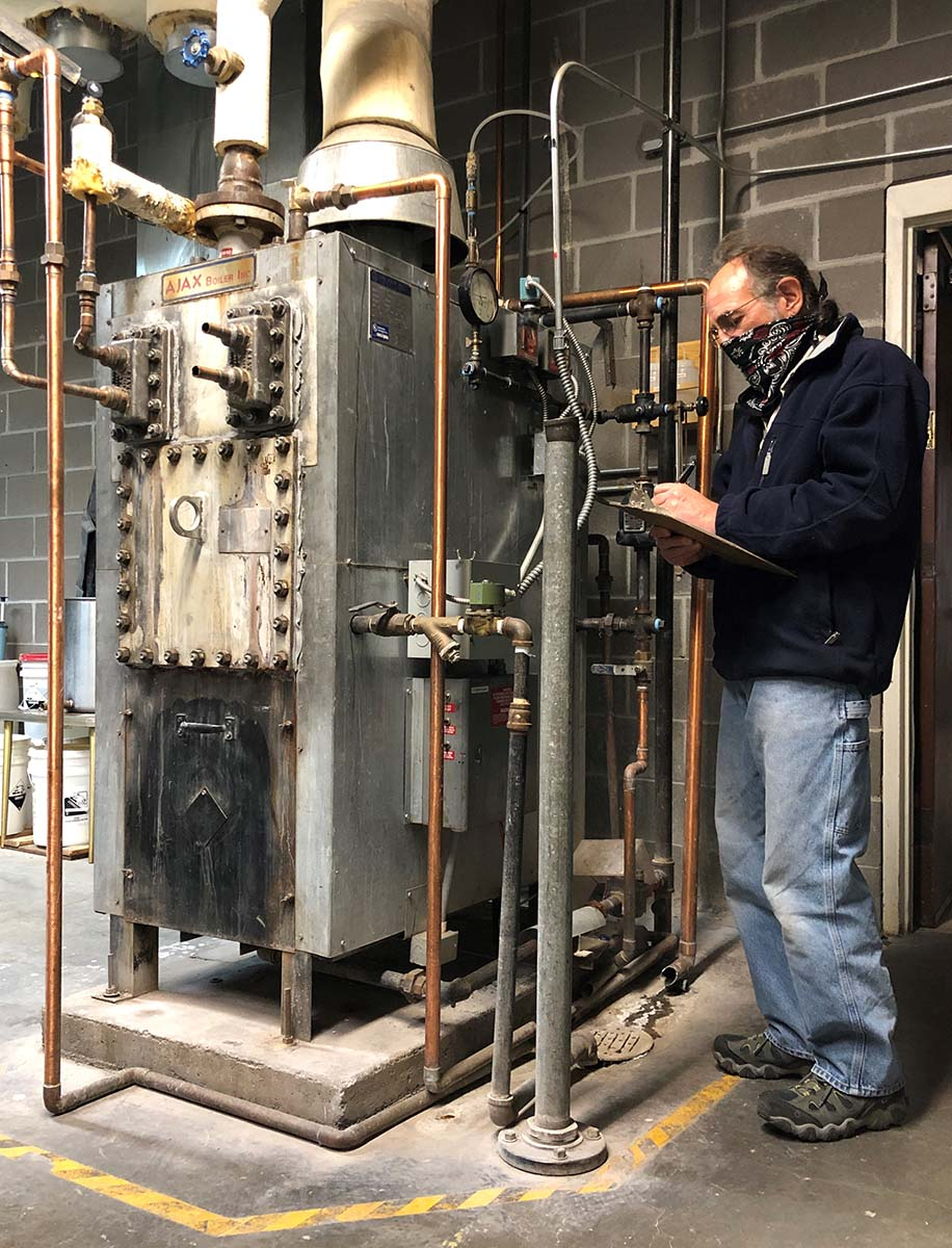 Operating Engineer Phil Anthony takes readings from the 30-year-old boiler in the Plains Indian Museum section of the Center. The only remaining steam boiler in the building, it is slated to be replaced with atomizer humidification.