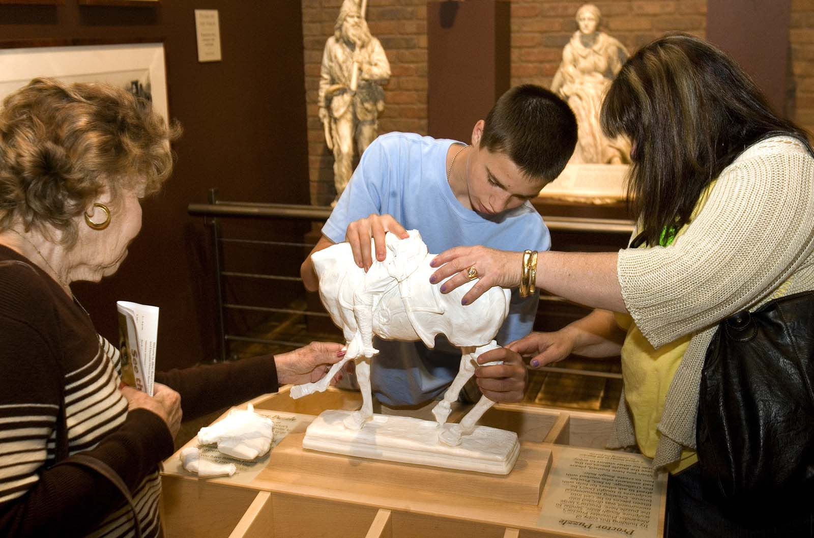 """On opening day, visitors try their hands at assembling a model of Alexander Phimister Proctor's monumental sculpture of Teddy Roosevelt, """"Rough Rider."""""""