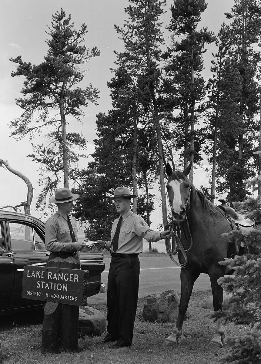 Bernie Packard, an assistant district range, gives work instructions to Ranger Bob Richard in Yellowstone National Park. Big Red, the horse, looks at the camera. MS 89 Jack Richard Photograph Collection, McCracken Research Library. PN.89.26.4322.18