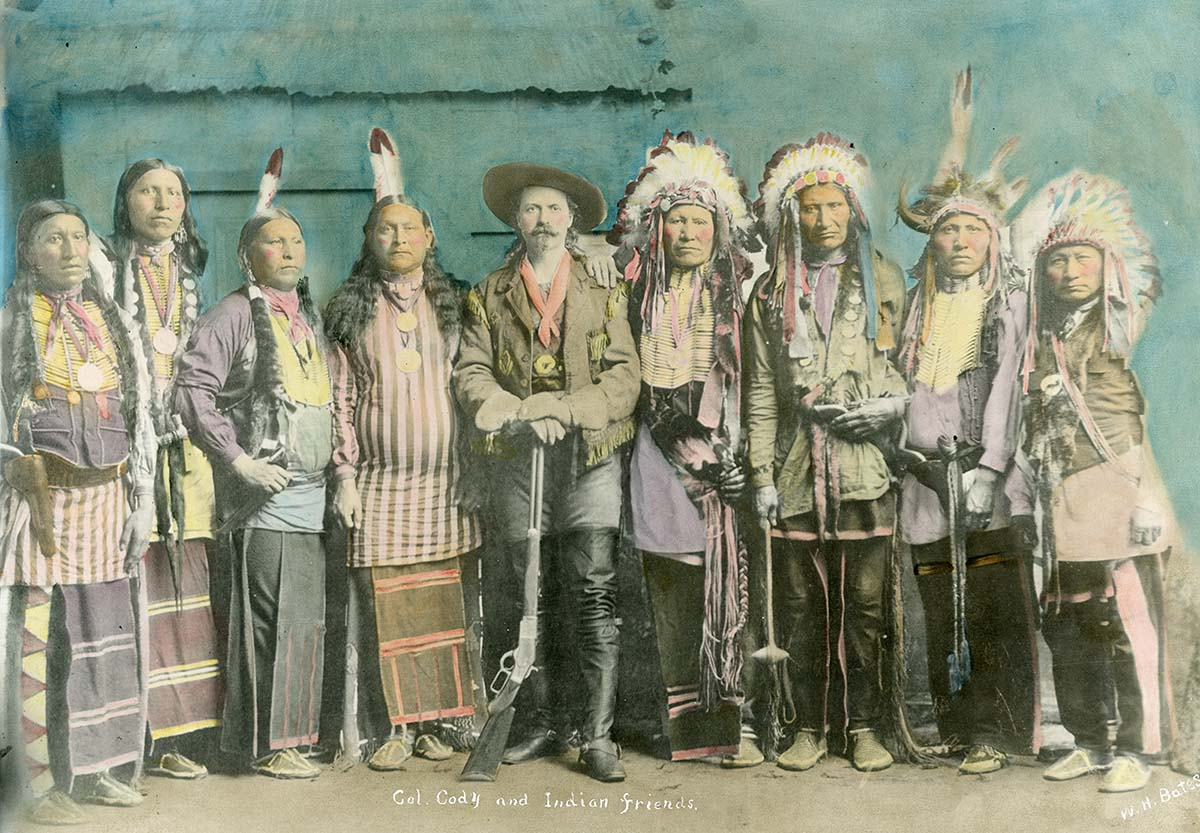 """A large number of images of Native Americans in Buffalo Bill's Wild West are posed photographs, some even in studios. Tom F. Cunningham describes how a special image he saw was anything but staged. (Hand-tinted photograph of William F. """"Buffalo Bill"""" Cody with his """"Indian Friends,"""" ca. 1886. MS 6 William F. Cody Collection, McCracken Research Library. P.69.813)"""