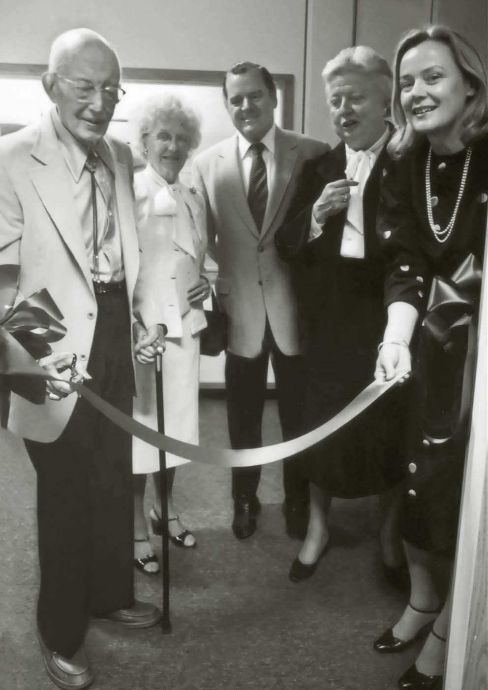 Dr. Harold McCracken, left, cuts the ribbon at the opening of the Buffalo Bill Historical Center's McCracken Research Library on August 15, 1980. He is accompanied, left to right, by Mrs. McCracken, Charles Duncan, Chair of the Center's Board of Trustees, Peg Coe, and Ann Duncan.
