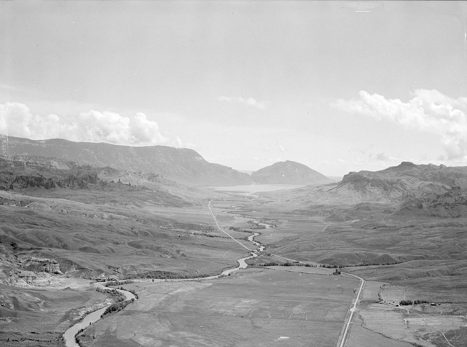 Aerial Aerial view of Wapiti Valley below with Rattlesnake Mountain on far left, Spirit (Cedar) Mountain center, and Sheep Mountain on right background. MS 89 Jack Richard Photograph Collection, McCracken Research Library. PN.89.29.4682.8of Wapiti Valley below with Rattlesnake Mountain on far left, Spirit (Cedar) Mountain center, and Sheep Mountain on right background. Hollister Ranch on bottom right with North Fork of Shoshone River flowing into Buffalo Bill Reservoir in background.