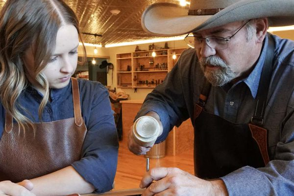 Scout Saddle Company master Keith Seidel (right) teaches leatherworking skills to apprentice Kali Shatto